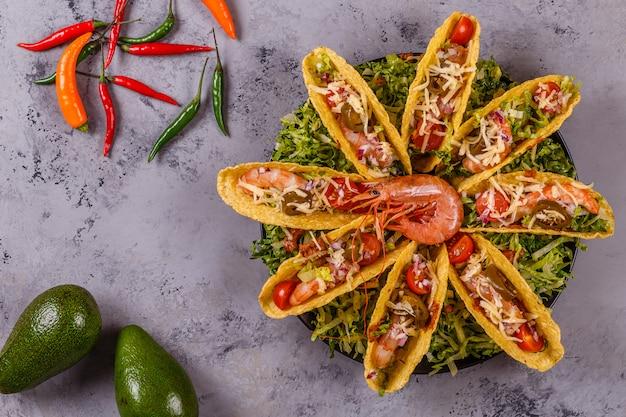 Tacos con gamberi, lattuga, formaggio e jalapeno.