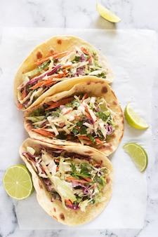 Tacos con guacamole e insalata di cavolo servito con fette di lime su uno sfondo chiaro.