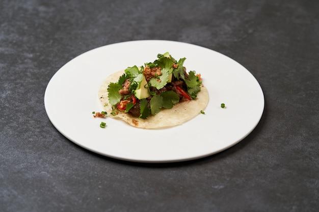 Tacos della via di carnitas della carne di maiale, primo piano. tacos messicani con carne di manzo, pomodori, avocado, peperoncino e cipolla