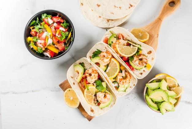 Tacos di tortilla di cibo messicano di frutti di mare con insalata di salsa fatta in casa tradizionale prezzemolo avocado di limone fresco e pedine di gamberi alla griglia