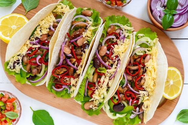 Tacos è un piatto messicano tradizionale. tortilla ripiena di pollo, campana e peperoncino, fagioli, lattuga, formaggio, cipolla blu con salsa di salsa su fondo di legno bianco. vista dall'alto. avvicinamento