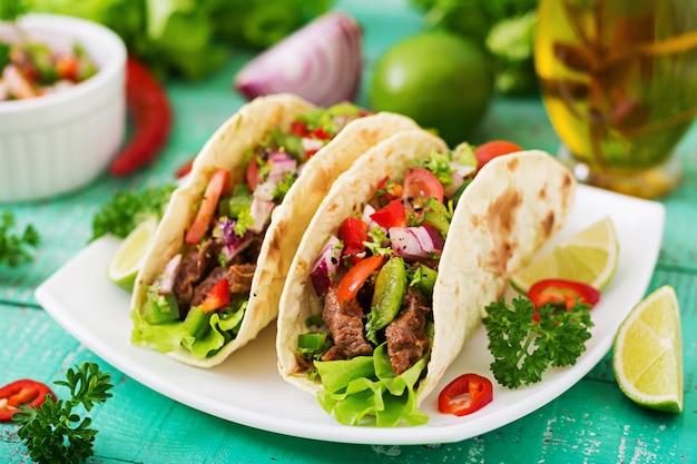 Tacos messicani con carne di manzo in salsa di pomodoro e salsa