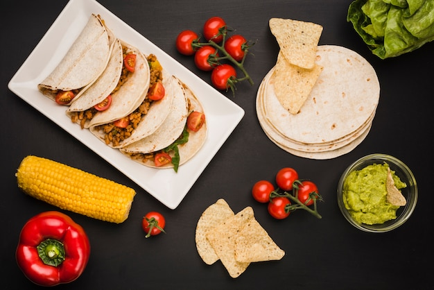 Tacos sul piatto vicino a verdure e salsa