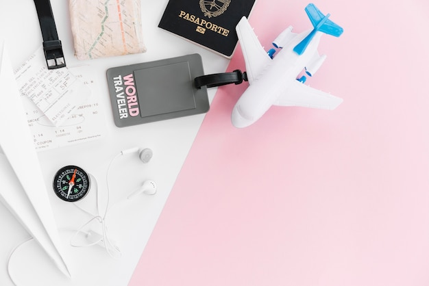 Tag del mondo viaggiatore con passaporto; carta geografica; bussola; biglietti; aeroplano giocattolo e auricolare su sfondo bianco e rosa