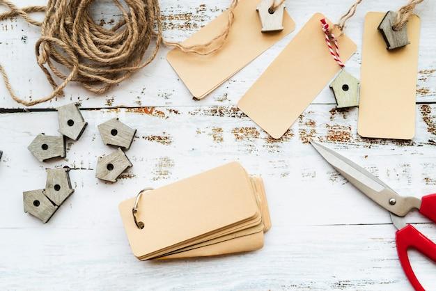 Tag vuoti; forbice; stringa e piccole nicchie sulla scrivania bianca