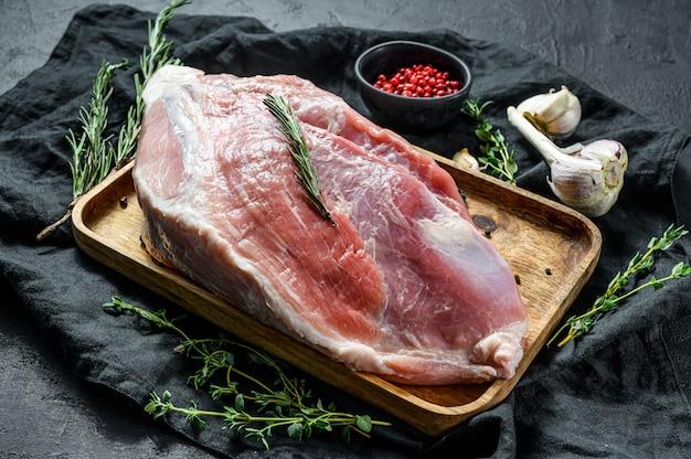 Tagli di maiale freschi. carne cruda con spezie. bistecca alla zampa posteriore. sfondo nero. vista dall'alto