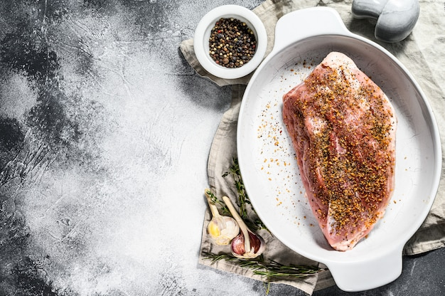 Tagli di maiale freschi. carne cruda con spezie. sfondo grigio. vista dall'alto