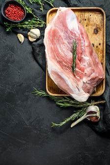 Tagli di maiale freschi. carne cruda con spezie. spalla butt parte .. sfondo nero. vista dall'alto