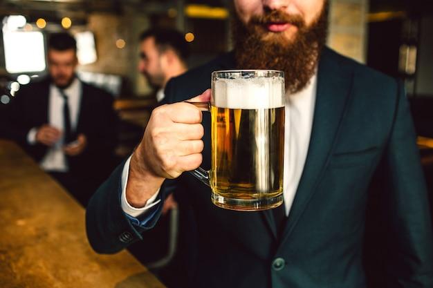 Tagli il punto di vista dell'uomo barbuto in tazza della birra della tenuta del vestito. altri due impiegati siedono dietro.