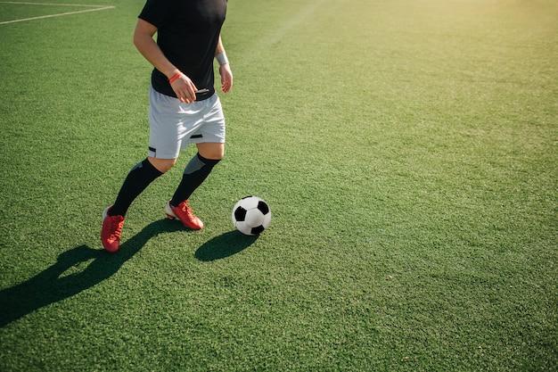 Tagli il punto di vista dell'uomo che gioca footbal da solo fuori. sta per calciare la palla.