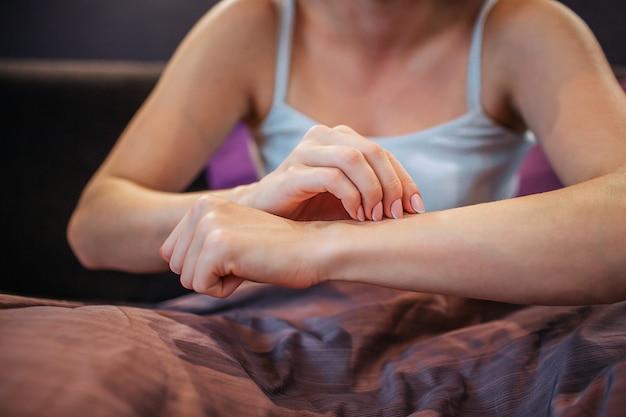 Tagli il punto di vista della giovane donna che si siede sul letto e che tocca la sua pelle con una mano. è sola nella stanza. le sue gambe sono coperte di coperta. la donna ha problemi.