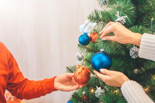Tagli il punto di vista delle mani uomo e donna che tengono i giocattoli di decorazione. ci sono colori rosso e blu.