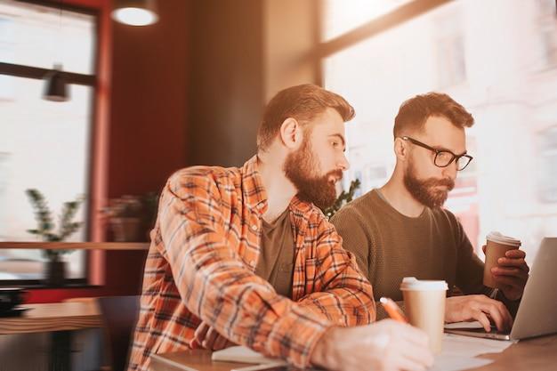 Tagli il punto di vista di due pantaloni a vita bassa che studiano nel caffè. uno di loro sta lavorando al computer mentre un altro è attento a ciò che sta facendo il suo partner.