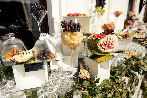 Tagli l'anguria si leva in piedi sul cubo di vetro sulla tabella con i frutti