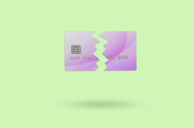 Tagli la carta di credito viola rotta isolata sulla priorità bassa della calce