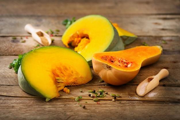 Tagli la zucca arancione matura con i semi e le erbe su di legno rustico. concetto di cibo sano biologico vegetariano e crudo, dieta.