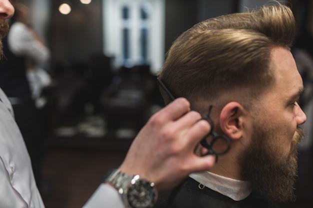 Taglia il barbiere tagliando i capelli dell'uomo barbuto