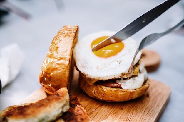 Taglia le uova sugli hamburger. preparando e facendo colazione a casa al mattino.