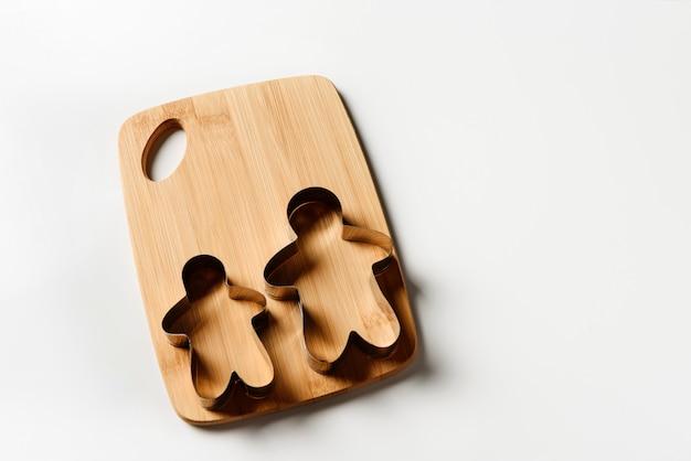 Tagliabiscotti per biscotti a forma di umano, distesi su un tagliere