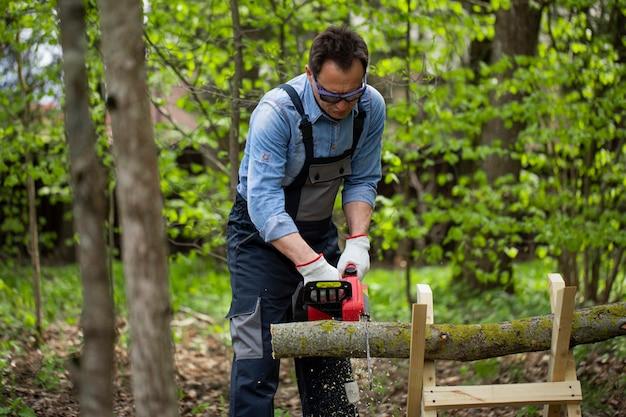 Taglialegna in legno di segatura uniforme funzionante con sega elettrica, cavalletto nella foresta