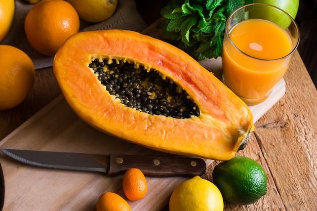 Tagliare a metà papaia matura, succo appena spremuto, agrumi, menta fresca sul tavolo di legno