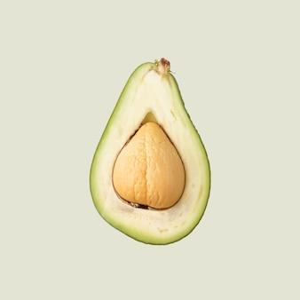 Tagliare a metà un avocado, un frutto tropicale su uno sfondo colorato.