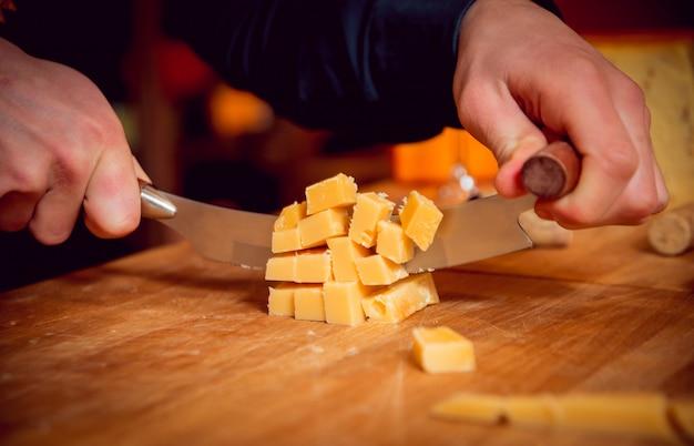 Tagliare con un coltello un pezzo di formaggio