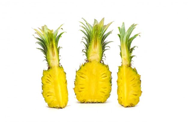 Tagliare i frutti di ananas a fette sulla superficie bianca