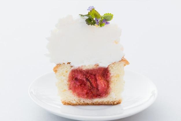 Tagliare il cupcake alla fragola con crema di formaggio e menta su un piatto bianco. avvicinamento