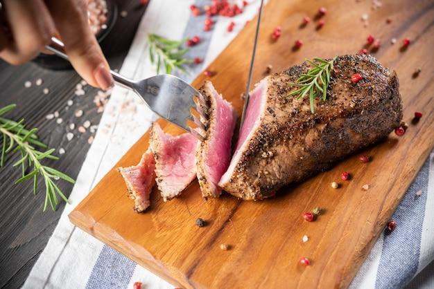 Tagliare il filetto di manzo arrosto con rosmarino e pepe
