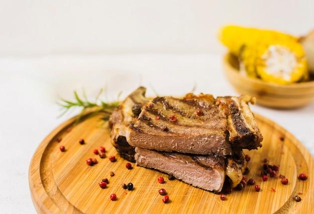 Tagliare la bistecca sulla tavola di legno