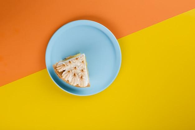 Tagliare la fetta di torta su un piatto blu