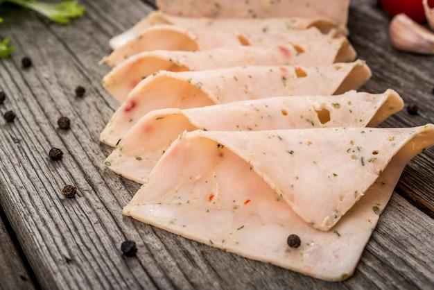 Tagliare la salsiccia dal prosciutto su un fondo di legno