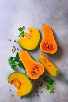 Tagliare la zucca arancia matura con semi ed erbe su grigio chiaro. concetto di cibo sano biologico vegetariano e crudo, dieta.