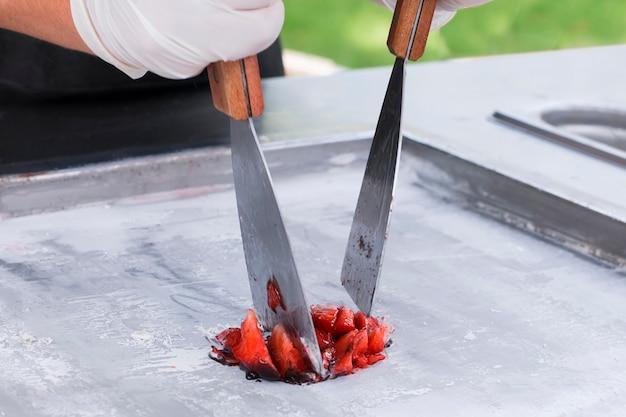 Tagliare le fragole a pezzi per il gelato tailandese