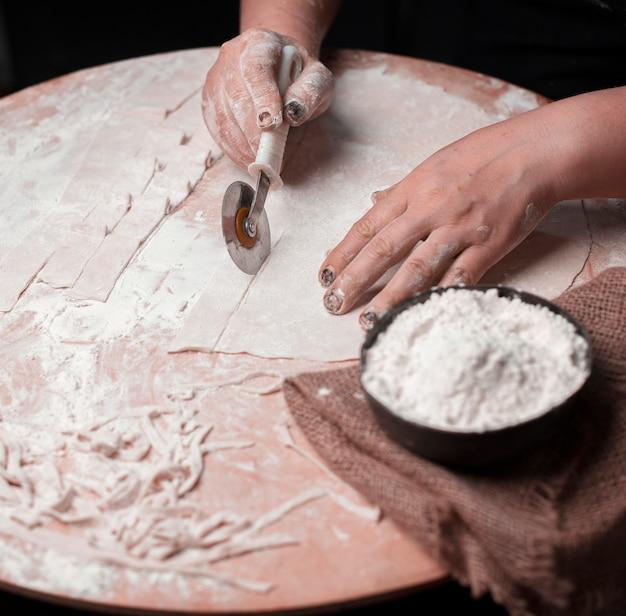 Tagliare le tagliatelle con pasta a strati fatta a mano.