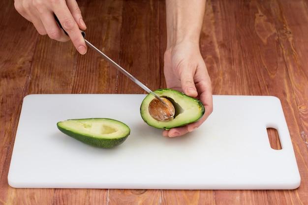 Tagliare le verdure con un coltello da cucina sul tavolo
