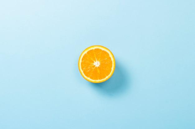 Tagliare metà dell'arancia su una superficie blu. minimalismo. concetto di tropici, alimentazione sana, vitamine. vista piana, vista dall'alto.