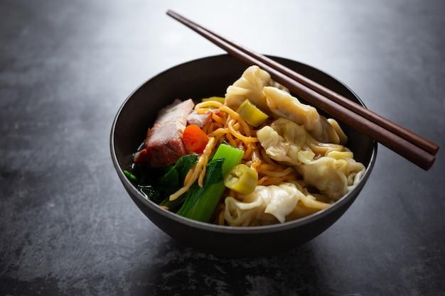 Tagliatella all'uovo con carne di maiale arrosto rossa e wonton sul tavolo.