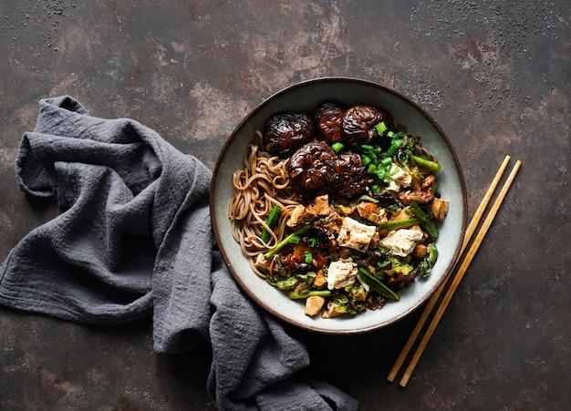 Tagliatella asiatica del soba del vegano con il formaggio del tofu, funghi di shiitake