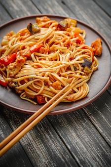 Tagliatella cinese in salsa agrodolce e bacchette sul tavolo