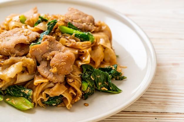 Tagliatella di riso in padella con salsa di soia nera e carne di maiale e cavolo, stile asiatico dell'alimento