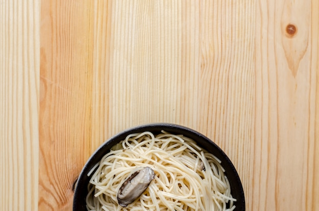 Tagliatella fritta in ciotola nera sulla tavola di legno, alimento tailandese della via