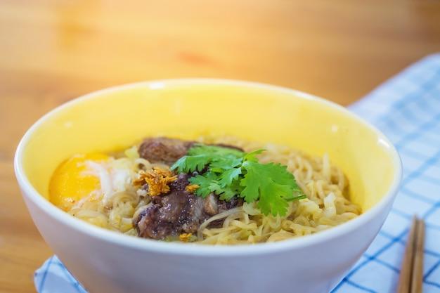 Tagliatella istantanea con carne di maiale e uovo pronto per essere mangiato - delizioso concetto di menu di cibo istantaneo