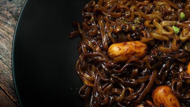 Tagliatella istantanea coreana in banda nera sulla tavola di legno per il contenuto alimentare.