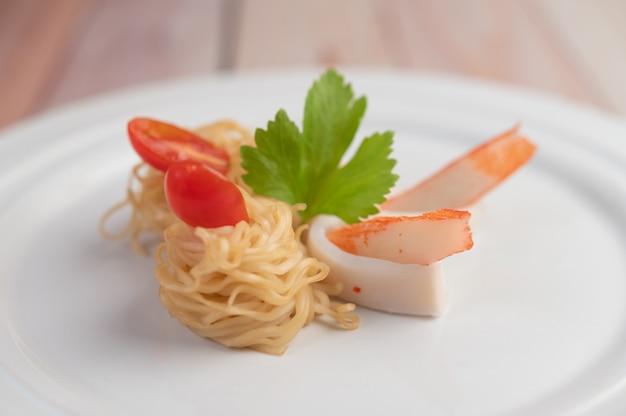 Tagliatella istantanea in padella con gamberi e bastoncini di granchio in un piatto bianco.