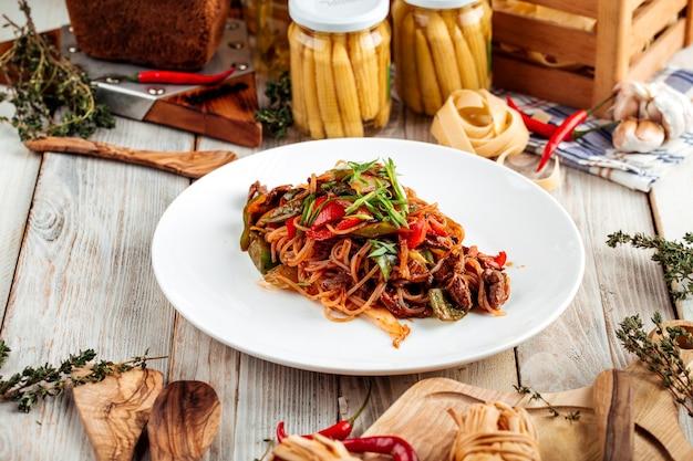 Tagliatelle asiatiche con carne di manzo e verdure nel piatto bianco