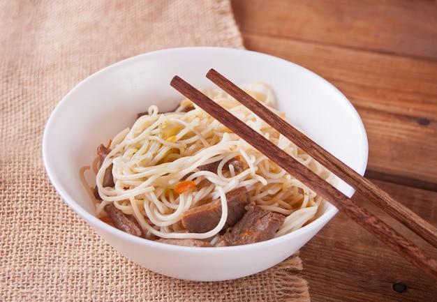 Tagliatelle asiatiche con manzo, verdure in ciotola con le bacchette, fondo di legno rustico. cena in stile asiatico tagliatelle giapponesi cinesi