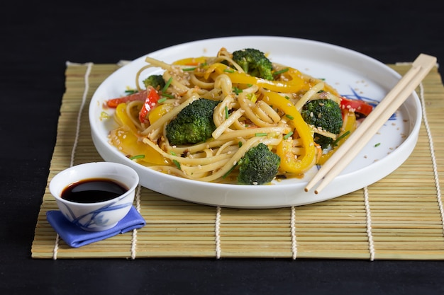 Tagliatelle asiatiche con verdure e salsa di soia sulla stuoia di bambù e bacchette, sullo sfondo nero