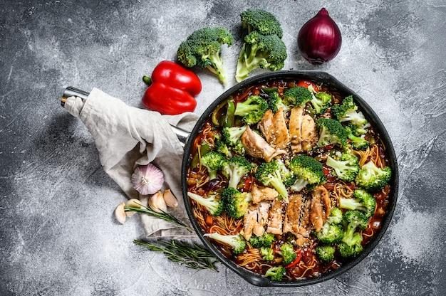 Tagliatelle asiatiche dell'uovo con le verdure e la carne sulla cottura della pentola. sfondo grigio. vista dall'alto. spazio per il testo